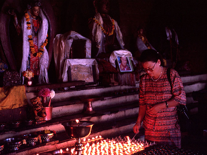 A woman lighting butter lamps in a Buddhist templeNikon FM2, 50mm, Fuji Velvia