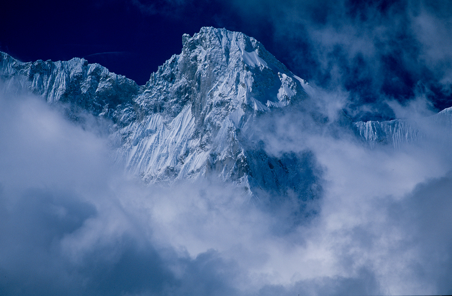 Part of the summit ridge, seen through breaking cloud from just below the Langma LaNikon F5, 180mm, Fuji Velvia 100