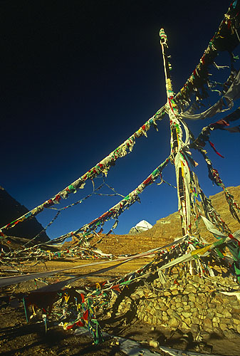 The huge ceremonial flag-pole at Darboche, with Mount Kailas just visible on the horizon. Kailas, known as Kang Rimpoche to the Tibetans, is believed to be the physical embodiment of the mythical Mount Meru, cosmic pillar of the universe. Here lives Demchhog, the Buddhist Shiva. Hindus similarly revere this mountain as tthe sacred throne of Lord Shiva. There is no other pilgrimage site of similar significance in either religion.Ngari, Western Tibet.Nikon FM2, 17-35mm, Fuji Velvia 100