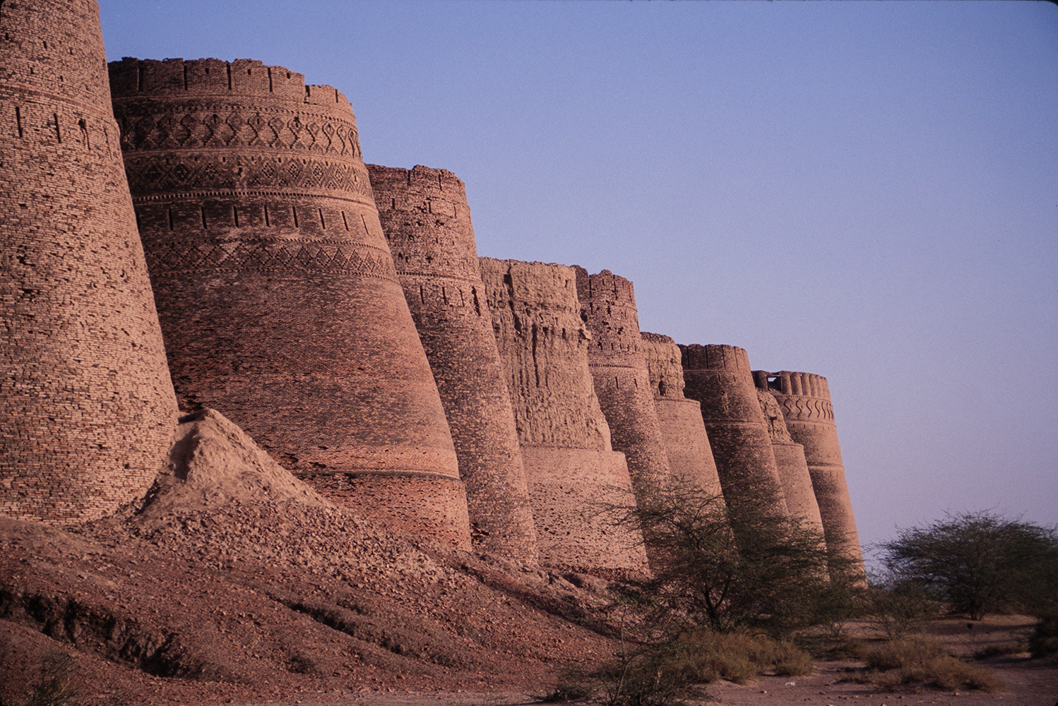 Close to Bahawalpur on the edge of the Cholistan desert, there has been a fort here for 5000 years as it is on the ancient trade route from Central Asia to India. The towers are 40 meters (130 feet) high and there are ten on each of the four sides. The whole is over a mile in circumference. The site was captured by the Abassi family from Raja Rawal Singh of Jaiselmer in 1733, and the present fort dates from that time. The area was once watered by the Ghaggar (Hakra) river, which was known in ancient times as the Sarasvati, along the 300 mile length of which are numerous arcaeological sites dating from the Indus Civilzation. In the 18th century some 12,000 people lived in the town below the walls of this fort.