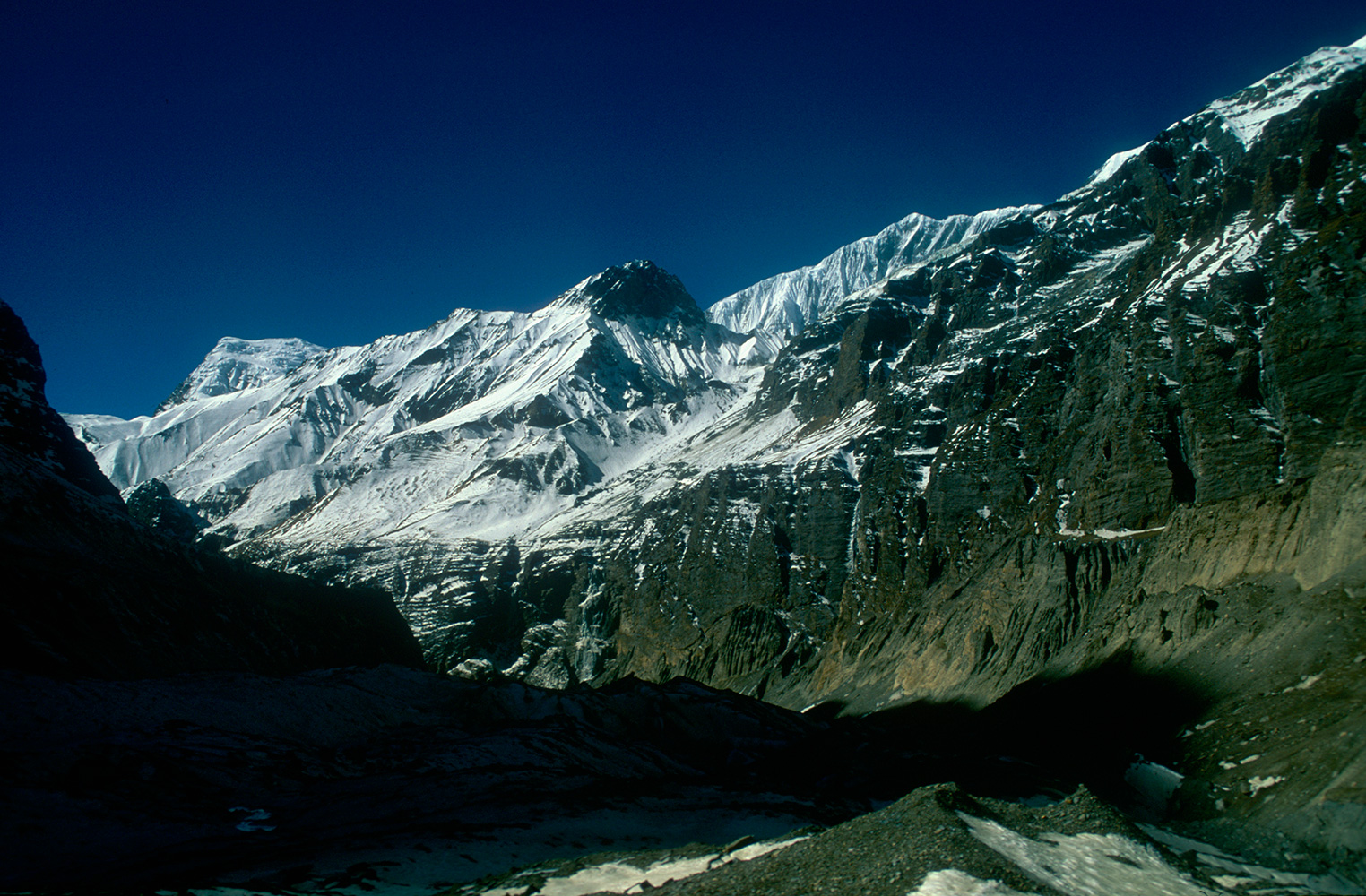 A view back south-west from the final approach to Dhaulagiri base-camp (4750m). The summit of Dhaulagiri V (7618m) is just visible, left of centre.Nikon FM2, 24mm, Fuji Velvia