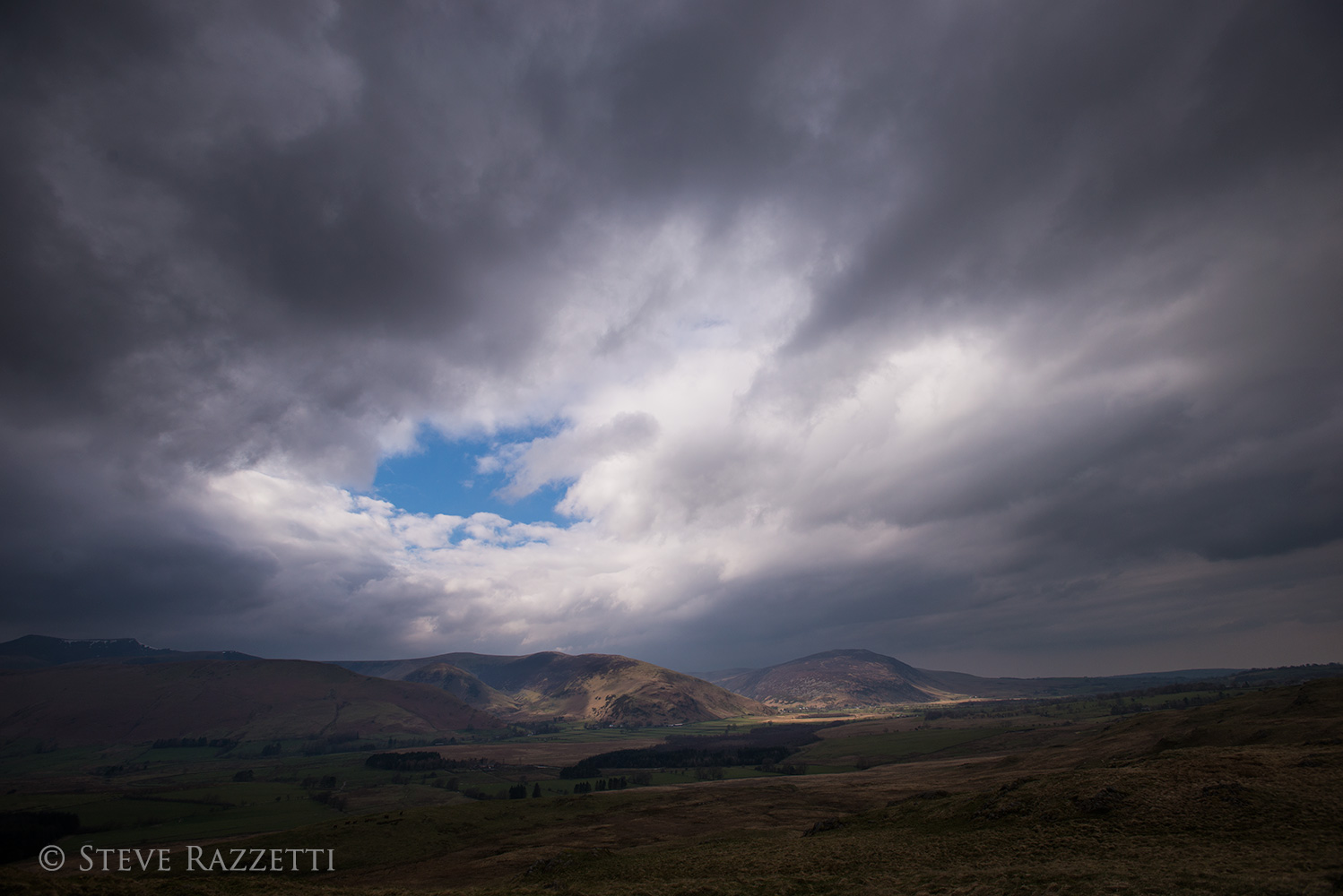A view to Mungrisedale and Mosedale, with Blencathra on the left, Bowscale Fell and Carrock Fell catching the sun under a stormy sky.