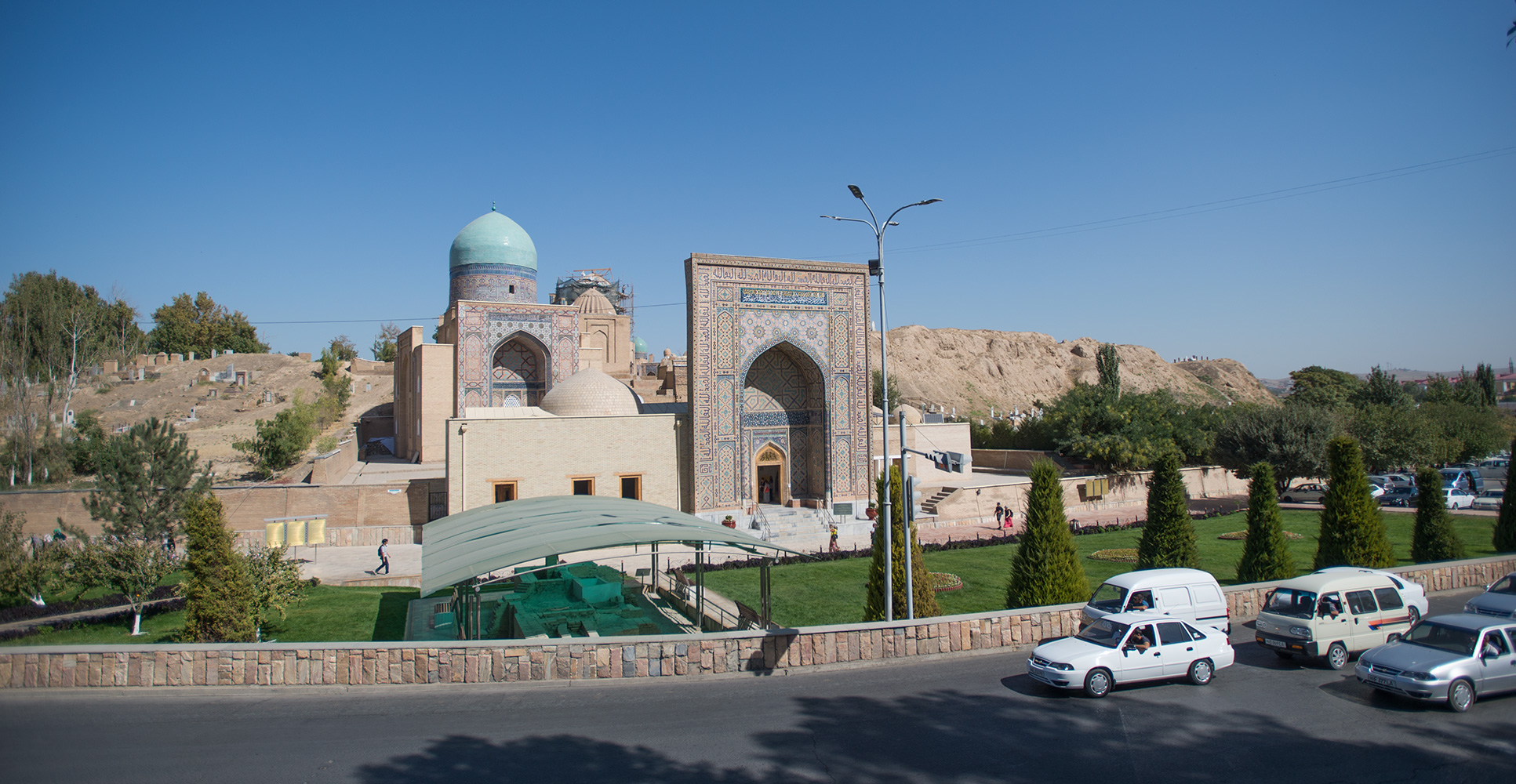 The complex from across the street in September 2018.Shah-i-Zinda means The Living King, and this is the holiest of all the archaeological sites in Samarkand. It is a vast necropolis of mausoleums dating from the 7th Century, but it is the structures dating from the 14th and 15th Centuries that really impress. Here, the ceramic artists of Emir Timur's time celebrated their craft, making it the most visually and atmospherically incredible place in the city.