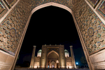 Seen through the entrance portal of the Ulug Beg Madrassah opposite. At night