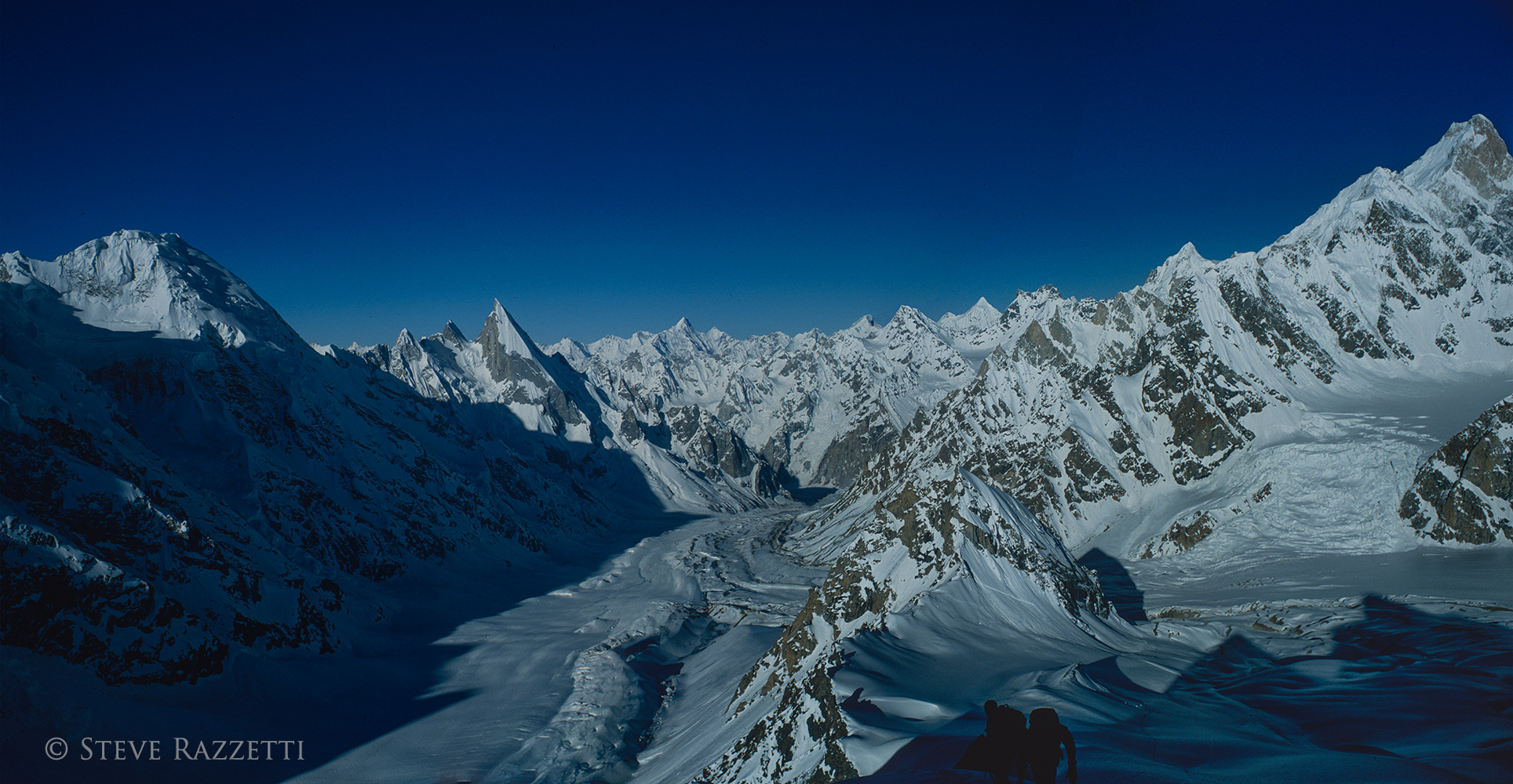 A panorama view down-valley from the summit of Gondogoro Peak (5650m), with Masherbrum on the far right, Trinity Peak on the far left, and the graceful spire of Layla Peak towering over the glacier. This is a stitch of two medium format colour slides (645) and the full resolution image is 6000 by 11000 pixels.