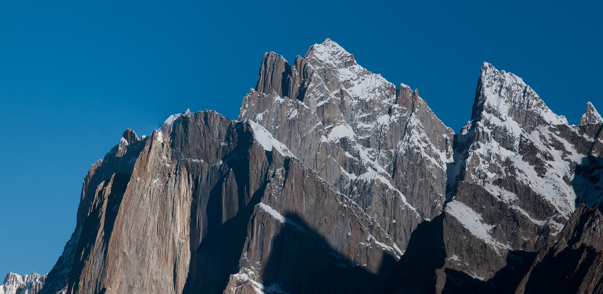 A stitch of two telephotos taken from Goro. Centre and left in the foreground are the upper ramparts of Cahedral (5607m), and on the right is the first Lobsang Spire (5428m). Towering above are the summits of Great Trango (6286m) and Trango Tower (6289m) and finally in the centre, towering above them all is Kruksum (6617m). This image was captured using a ten year old 12 mega pixel Nikon D300 and a 180mm f2.8 Nikkor prime lens. On a tripod of course. Pixel counts and the latest gear are no substitute for clear air quality glass and gorgeous light in the mountains! This is one of my favourite pictures from this trip. Incredible mountains!