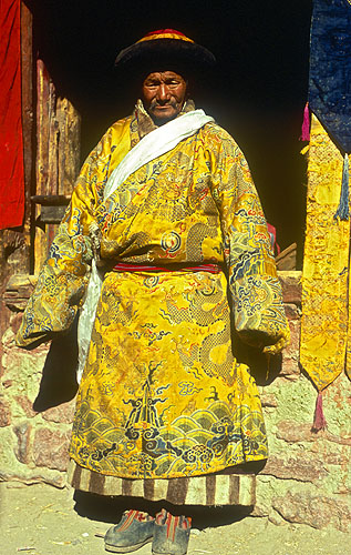 An old man from Halji village in Limi, north-west Nepal, in his ceremonial clothes. These lavishly embroidered silk were brought from Tibet when the village's monastery was founded, and are approximately one thousand years old.Nikon FM2, 17-35mm, Fuji Velvia 100