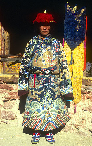 A village elder sporting his ceremonial clothes. These sensational embroidered silks were brought from Tibet at the time of the foundation of the village's gompah (monastery), and are approximately 1000 years old.North-west Nepal.Nikon FM2, 17-35mm, Fuji Velvia 100