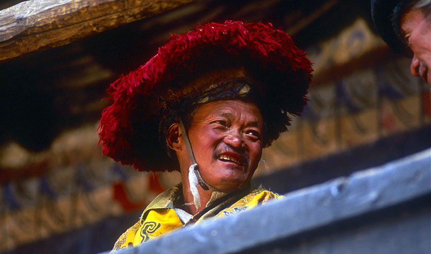 A villager chatting with friends during a break in festival proceedings at the monastery.North-west Nepal.Nikon FM2, 17-35mm, Fuji Velvia 100