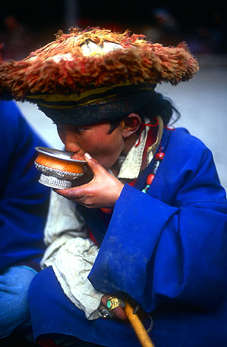 A boy taking a sip of Tibetan butter tea during a break in festivities.North-west Nepal.Nikon FM2, 17-35mm, Fuji Velvia 100