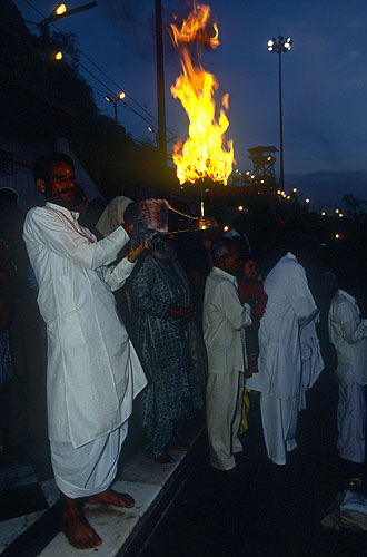 As dawn breaks on the morning of the mela, devotees offer their pujas and salute the rising sun with fireNikon F5, 17-35mm, Fuji Velvia 100