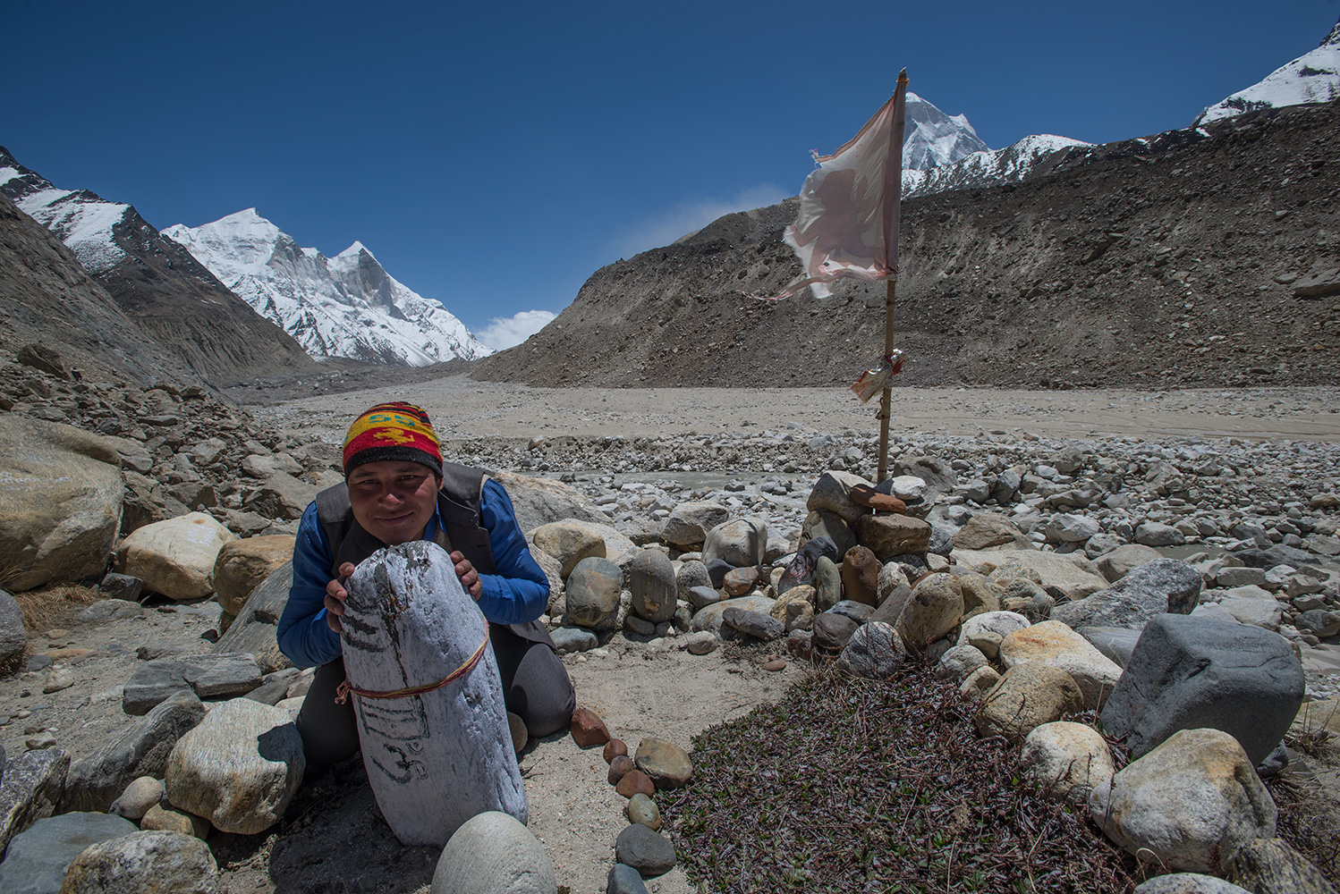 One of our porters poses with a Shival Lingum with Gaumukh and the snout of the Gangotri glacier beyond. Bhagirathi npeaks ahead and Shivling behind the flag to the right.