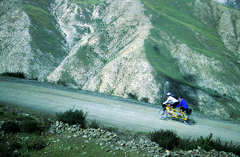 Ken and Cindy Dowling cranking it out on their tandem on the descent from the Kamba La to Yamdrok Yam Tso (lake) on the old road from Lhasa to GyantseNikon FM2, 105mm, Fuji Velvia