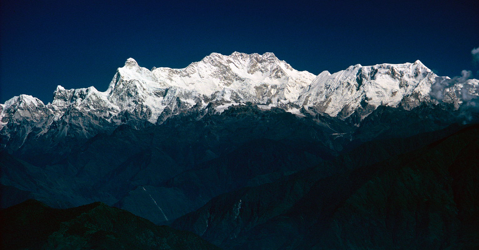 My first view of the Kangchendzonga massif, from the crest of the Milke Danda ridge. In 1988 Rex Munro and I made a 40 day trek across eastern Nepal, starting at the airstrip at Tumlingtar. After Makalu base camp we headed east via Chainpur and the Milke Danda to Taplejung. This picture was taken from the Milke Danda near Chauki.Canon A1, 135mm, Kodachrome