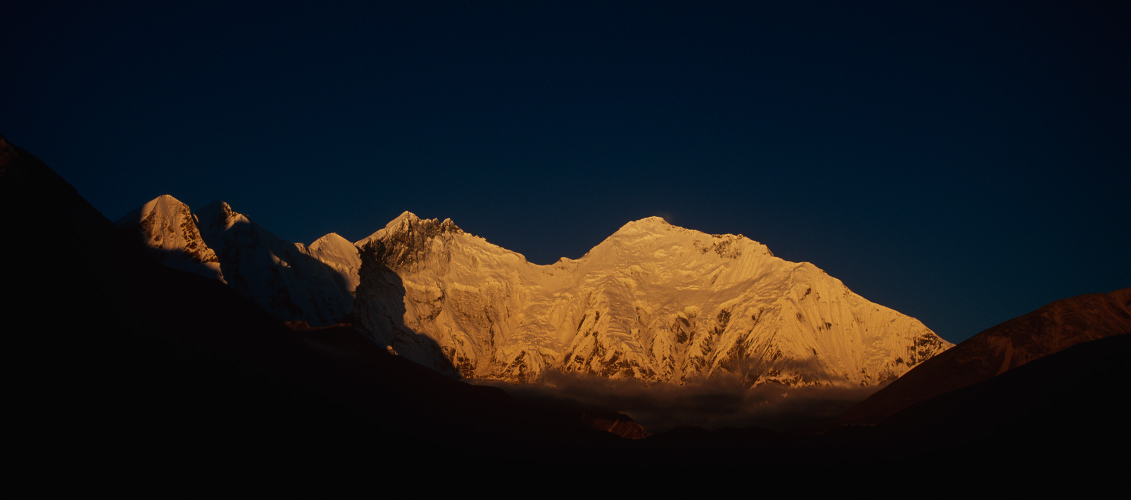 The first rays of sun illuminate the east faces of Lhotse and EverestNikon F5, 17-35mm zoom, Fuji Velvia 100