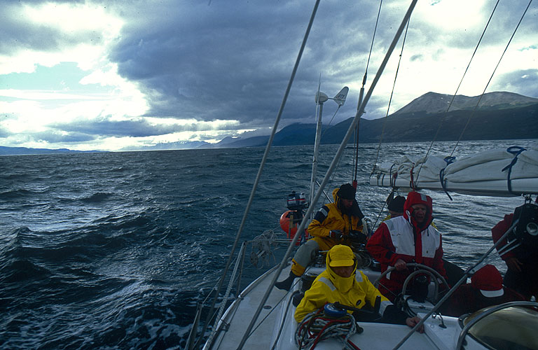 With sails furled and motor running, the Kekelestrion rounds Peninsula Guardiamarina Zanartu, which protects the harbour at Puerto Williams, and enters the calm, protected haven of the port. In the background across the water is Isla Grande.Nikon FM2, 24mm, Fuji Velvia