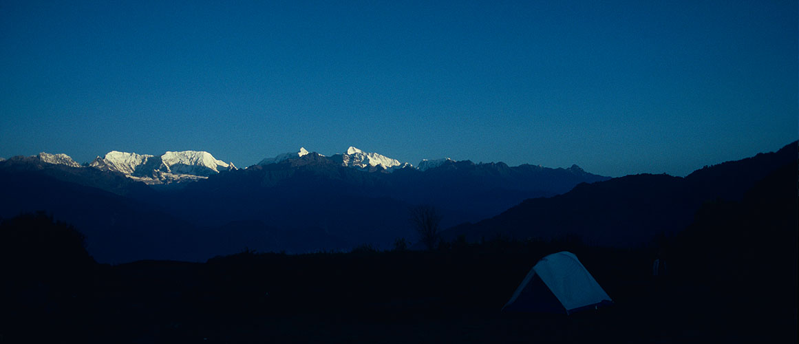 The trail from Tumlingtar soon climbs onto a ridge commanding excellent views north towards Makalu. In this shot, from a camp near the village of Mure, Makalu, Baruntse and Chamlang catch the first rays of sun in the morningCanon A1, 28mm, Kodachrome 64