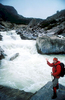 On a wild and windy day, Dr Natalie Hawkrigg pauses by the milky torrent that issues from the snout of the enormous glacier that cascades from the east face of San Lorenzo.Nikon FM2, 24mm, Fuji Velvia