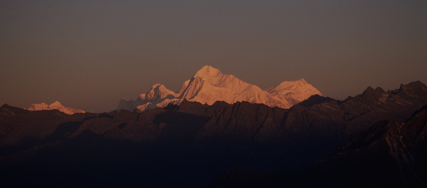 Pathi Bara is a 3700m top just north of Taplejung in Eastern Nepal. There is a tiny Shiva shrine there. At the end of our 1988 trek I spent a night sleeping at the shrine with a group of pilgrims. This is the view that greeted us early the next morning - sunrise light on Makalu, Lhotse and Chomolonzo.Canon A1, 135mm, Fuji RFP