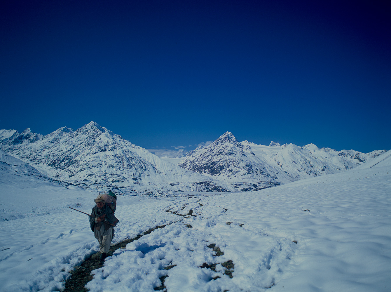 After a summer snowstorm, this porter is approaching the crest of the Karumbar at 4188m. The pass separates Chitral from Ishkoman, and is crowned with a spectacular turquoise lake.Bronica ETRSi, Fujis Velvia