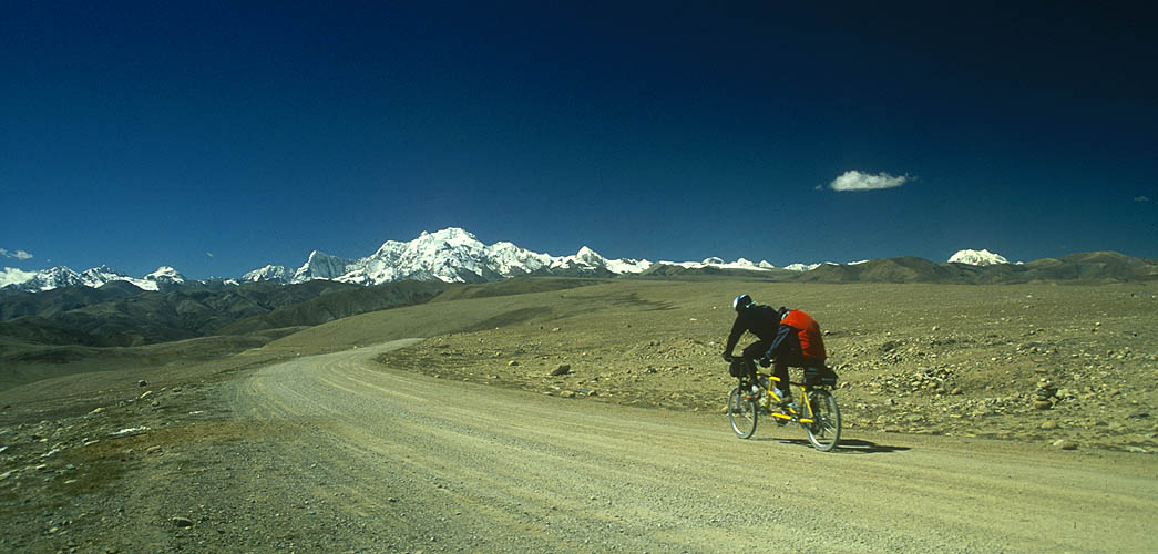 Heading south across the Tang La towards Nepal, Ken and Cindy Dowling ride their tandem beneath the snow-plasterd bulk of Shishapangma (8046m), the only one of the world's 14 8000m peaks that lies wholly within Tibet.Nikon FM2, 24mm, Fuji Velvia