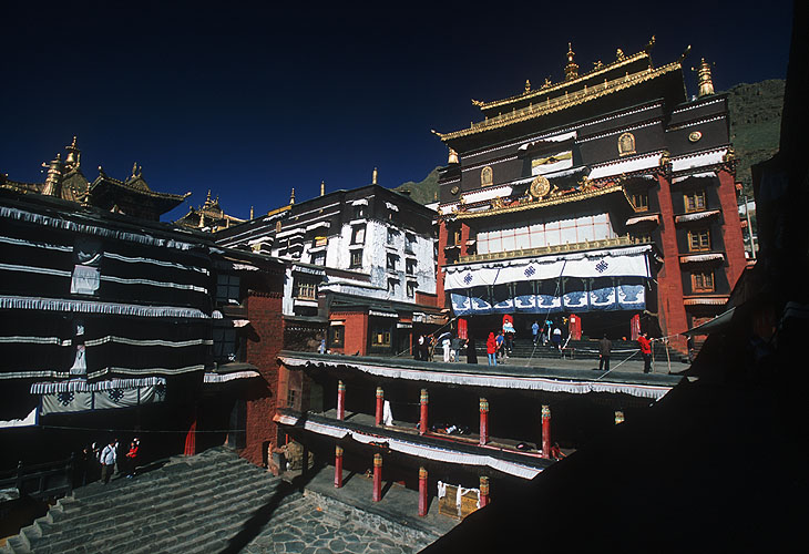 The Kelzang Kyamra is the great courtyard where ceremonial dances are performed during festivals. This view is lookong west to the Dukhang or Assembly Hall - the oldest building at Tashilhunpo. The Panchen Lama has been more accommodating than most Tibetans to the Chinese since the invasion, and this may help to explain the $10 million the latter have reputedly lavished on refurbishments hereNikon F5, 17-35mm, Fuji Velvia 100