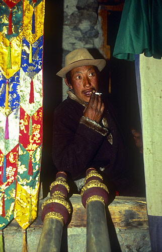The monk charged with blowing the ceremonial horns during a festival at this remote monastery sneaks a cigarette during a quiet moment.North-west Nepal.Nikon FM2, 17-35mm, Fuji Velvia 100