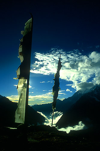 Prayer flags silhouetted against the sun in the summit.Nikon FM2, 24mm, Fuji Velvia