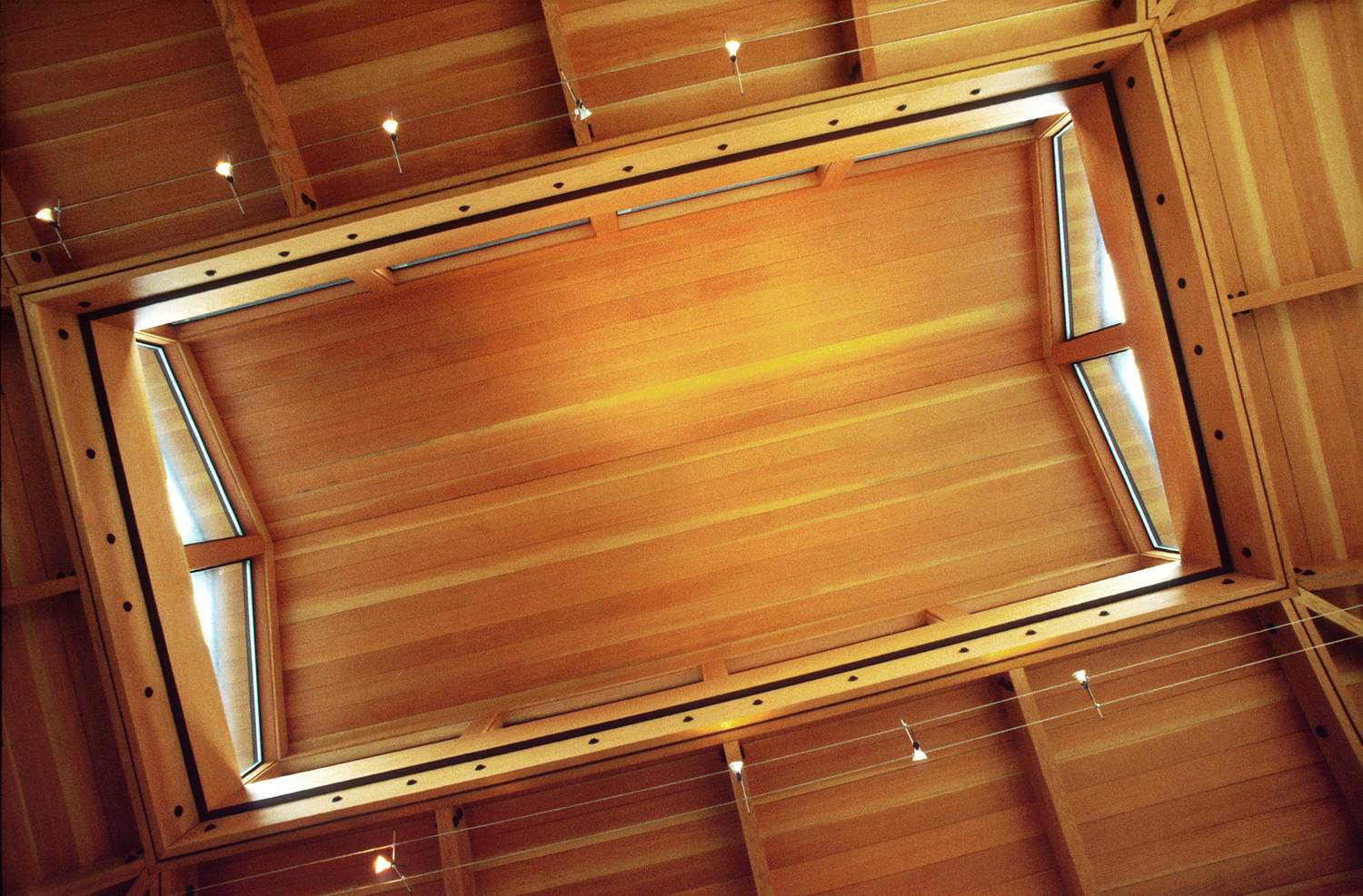 The ceiling is made of clear, recycled Douglas fir. A composite steel-and-wood rigid frame surrounds the lantern and reaches down to the walls, allowing a light and open structure.