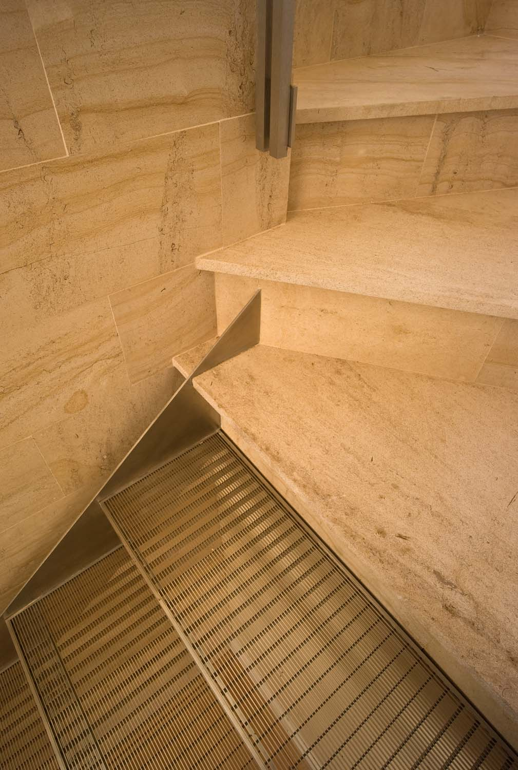 The transparency and lightness of the stainless steel stair set against the limestone winder