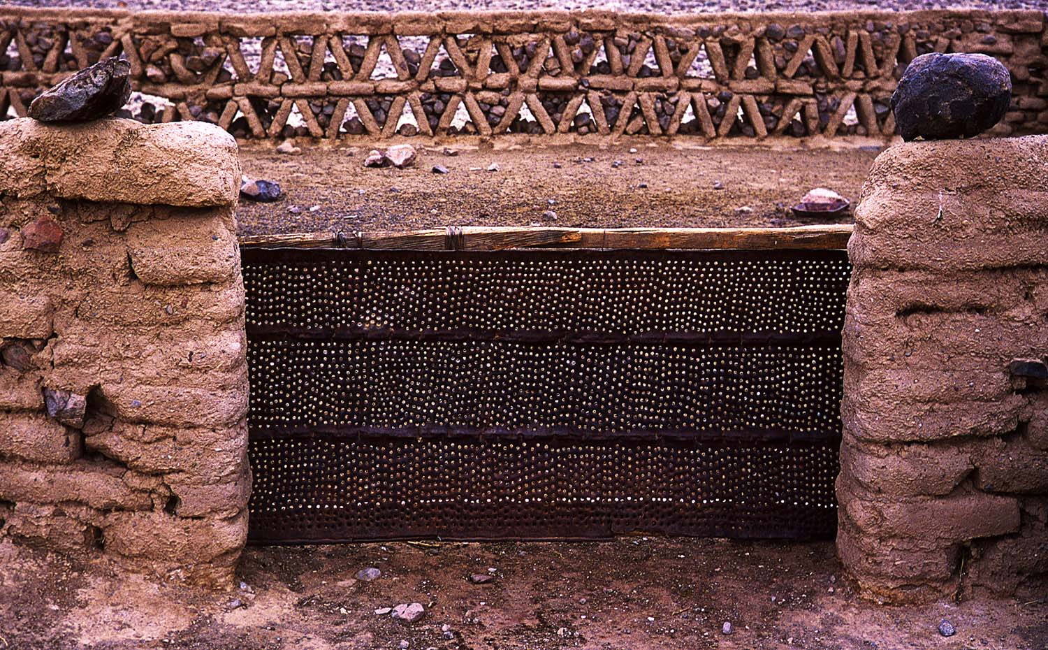 Adobe and stone corral with flattened, perforated steel drum gate.Corral de adobe y piedra con puerta de latón de acero, aplanada y agujereada.