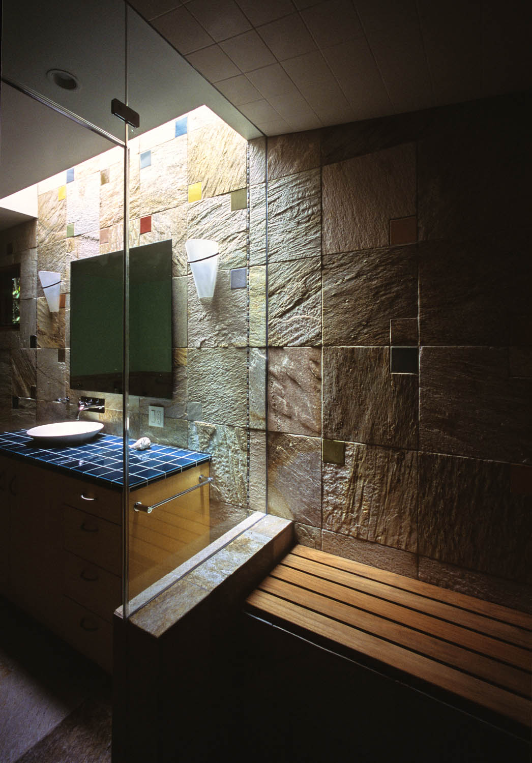 The master bathroom has a long skylight that washes light over a long wall of stone, changing in mood and intensity over the course of the day.