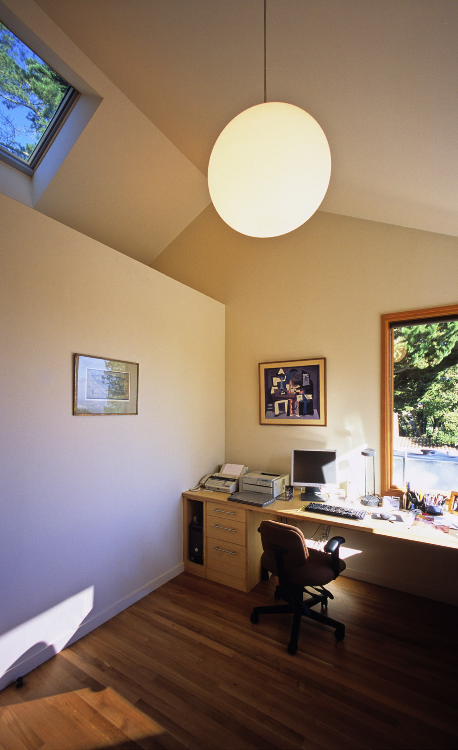 A skylight over a light shelf expands the sense of openness and the play of natural light.