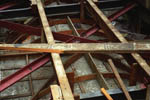 A horizontal steel truss inserted above the aisles bridges between south and north shear walls. The original self-supporting plaster vaults , framed in wood, can be seen below the truss.