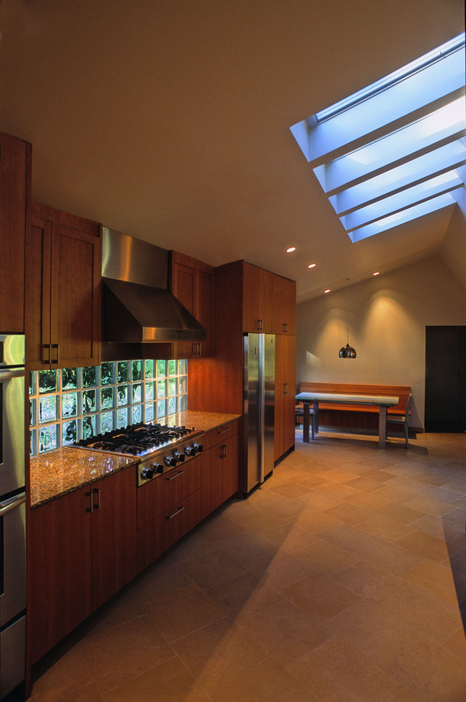Solid glass block backsplash, limestone floor, bank of operable skylights add up to a warm, light-filled kitchen