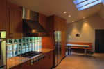 Solid glass block backsplash, limestone floor, bank of operable skylights add up to a warm, light-filled kitchen