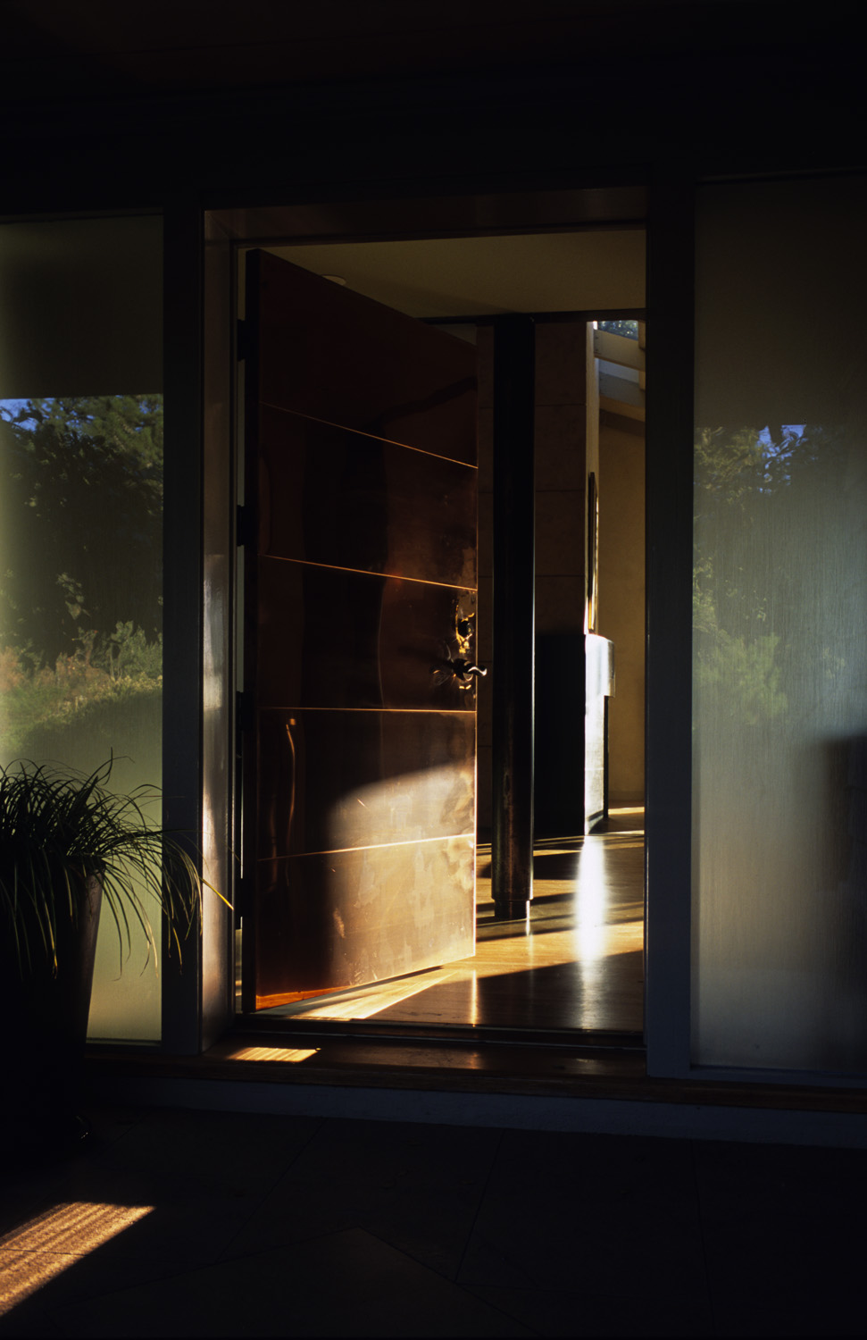 Copper-sheathed entry door flanked by translucent glass panels