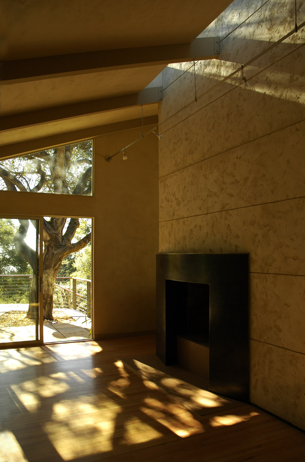 Den fireplace wall lit by a full-width skylight.