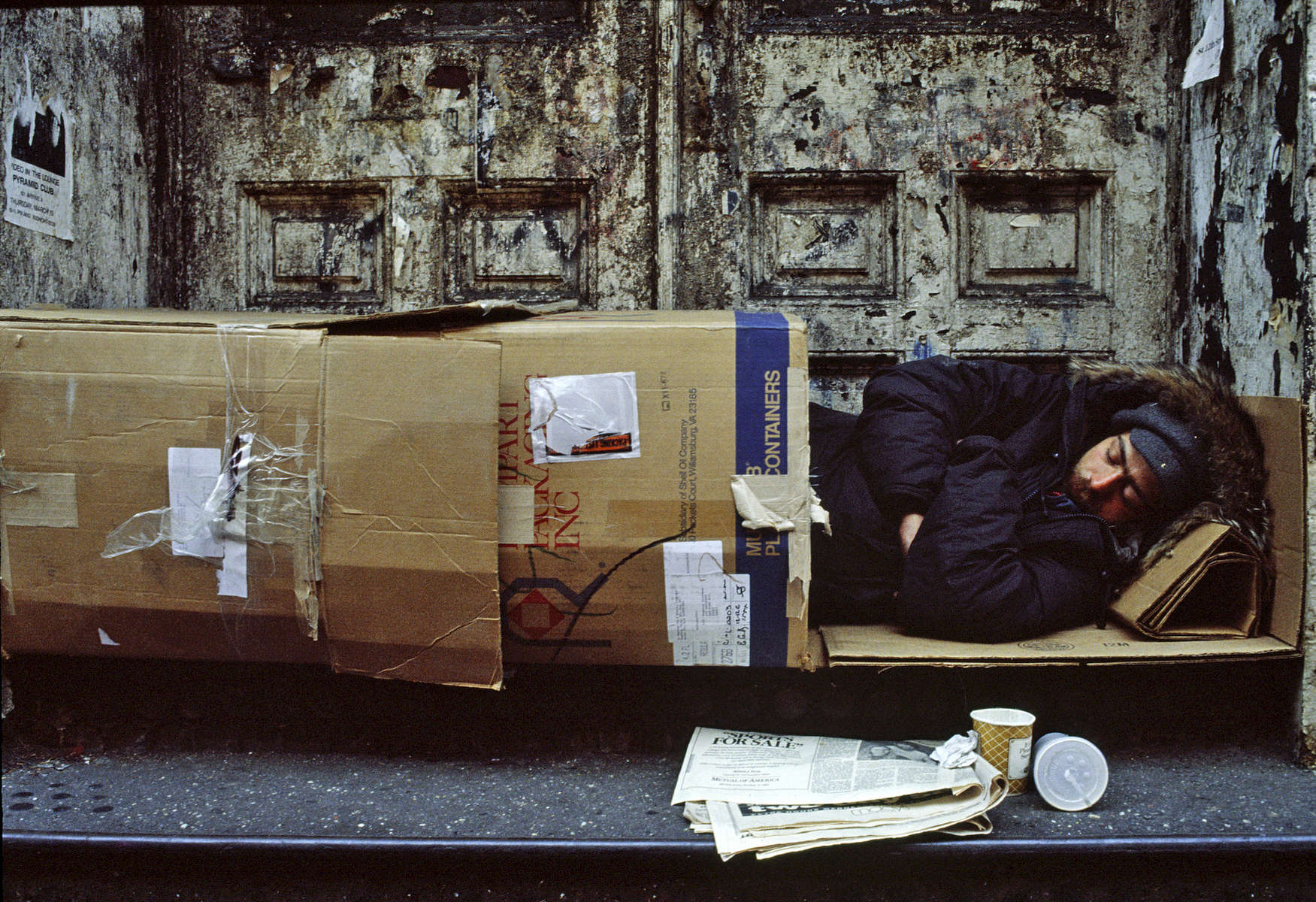 Homeless man sleeping in a cardboard box.