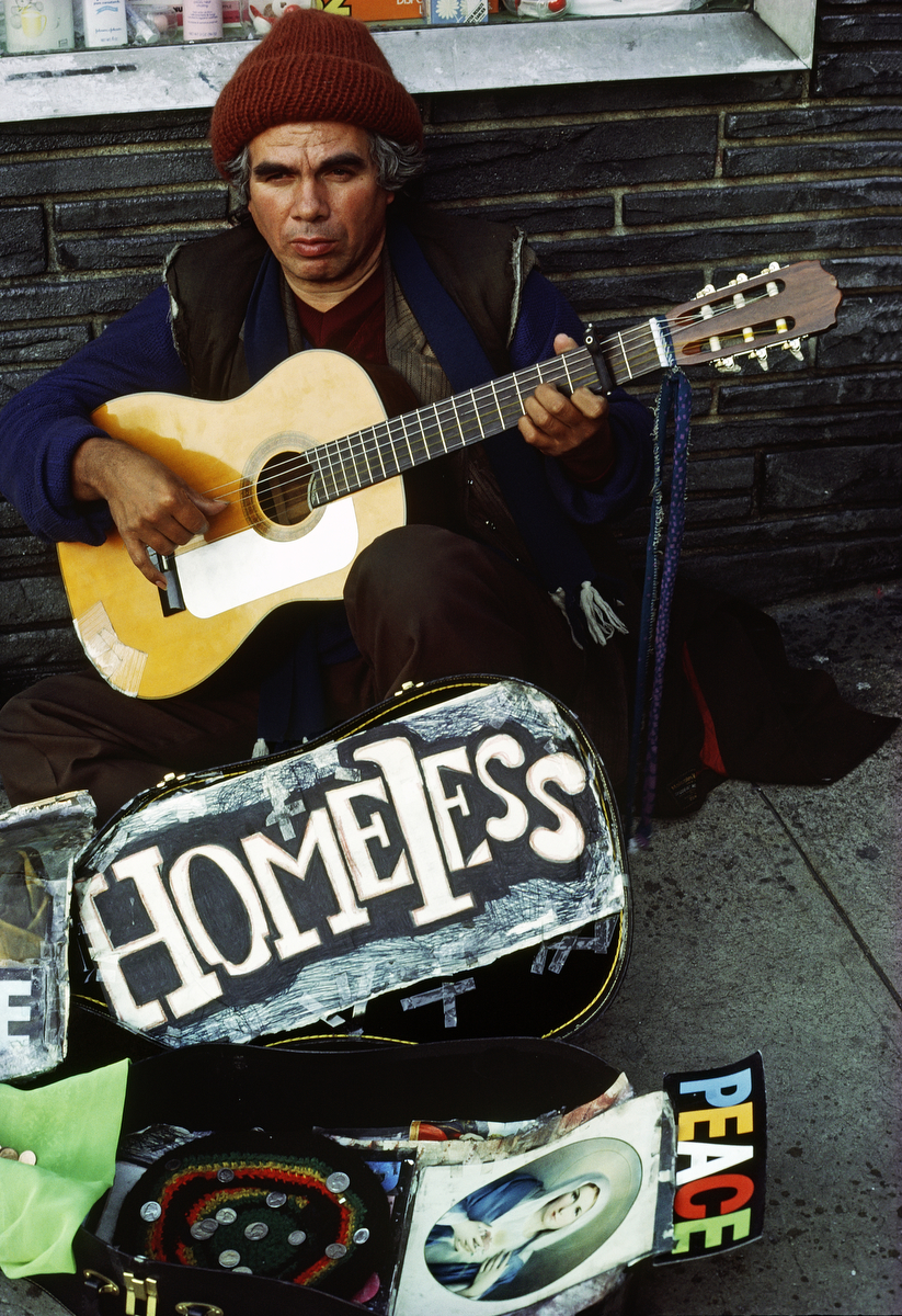 October 1987 - Homeless street musician playing his guitar to make money.