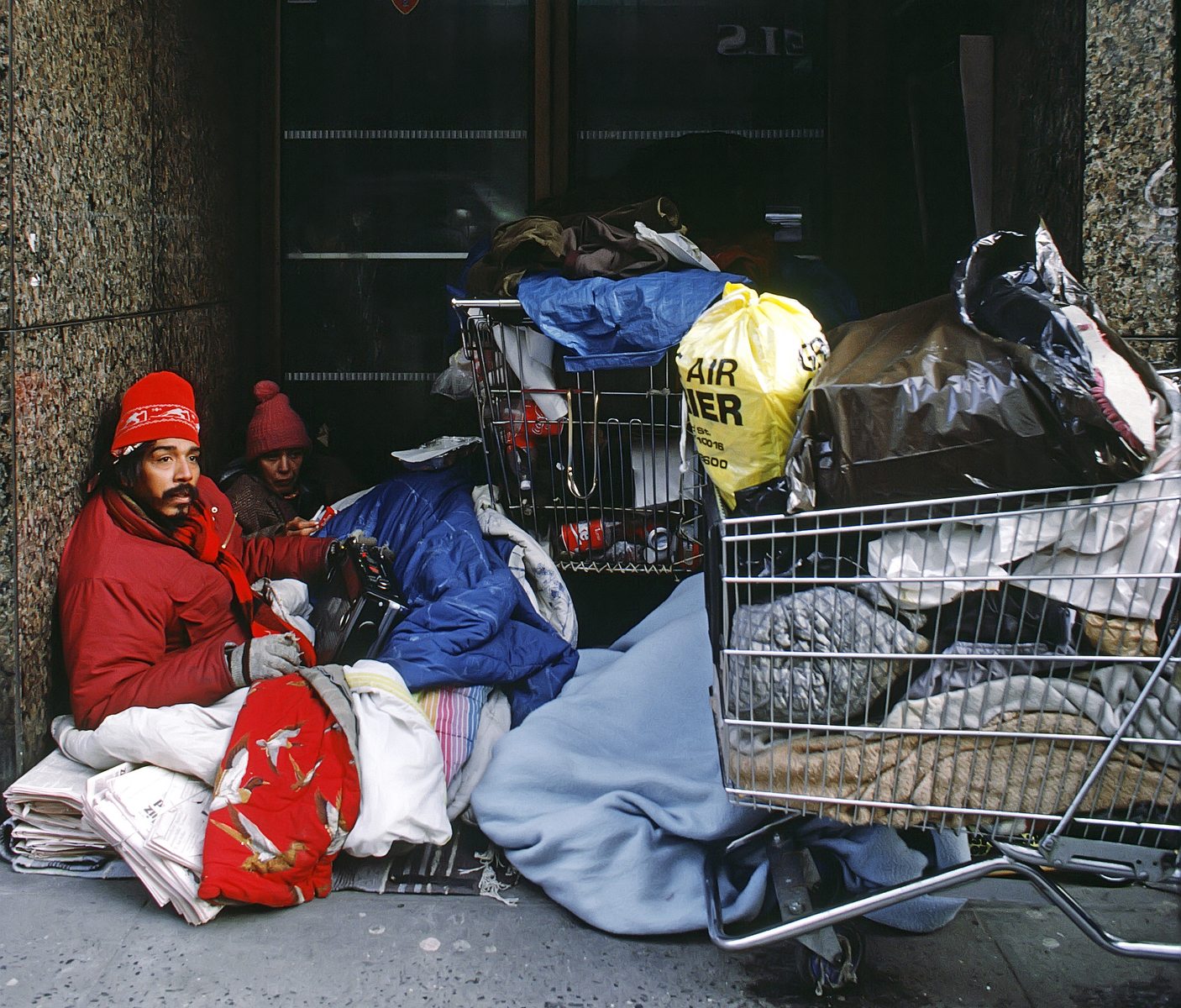1999 - Homeless couple living on the streets of New York City with shopping carts.