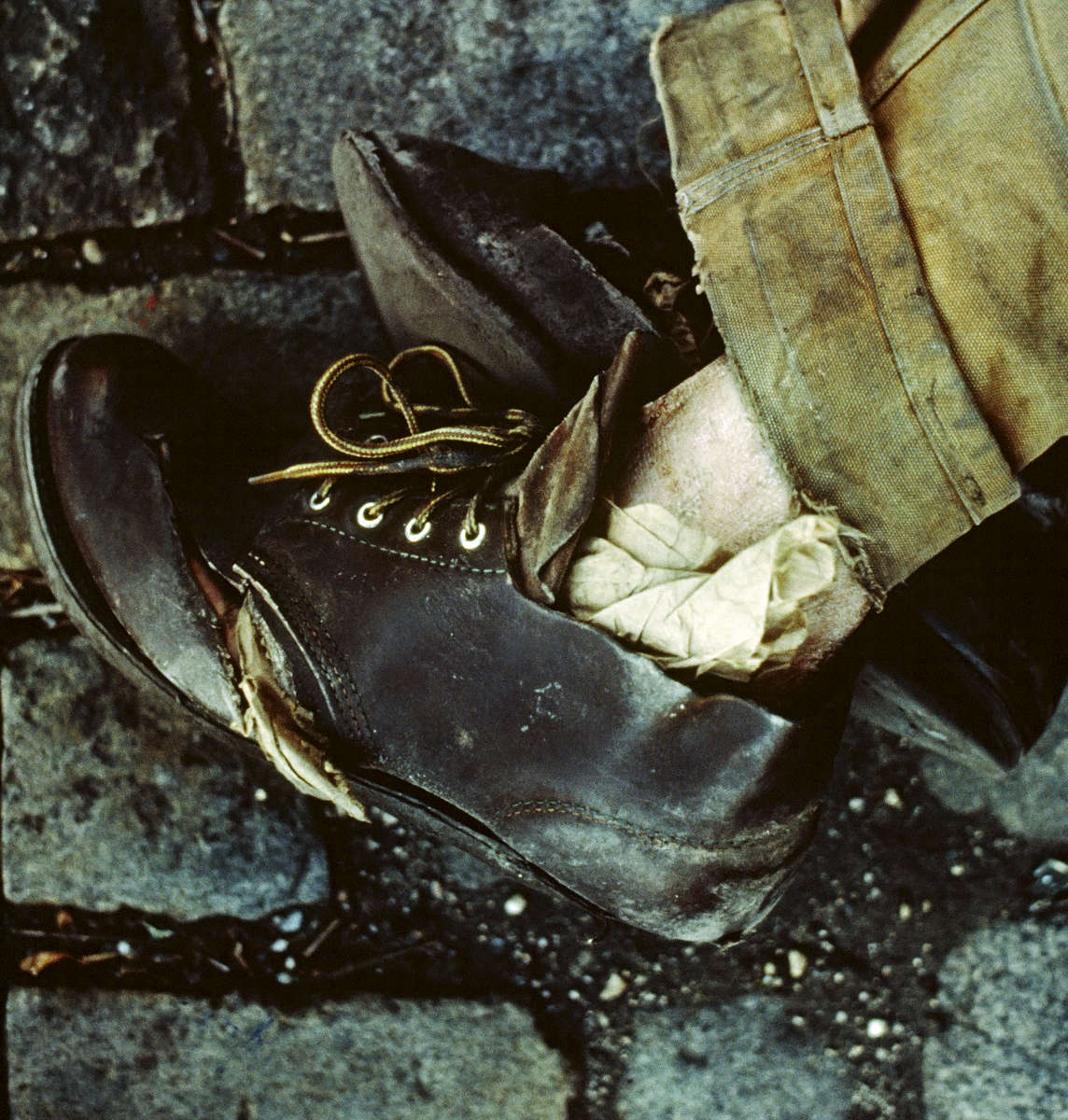 November 1987 - Homeless man sleeping on the streets of New York City, without socks, stuffed paper into his shoes to keep his feet warm in the winter.