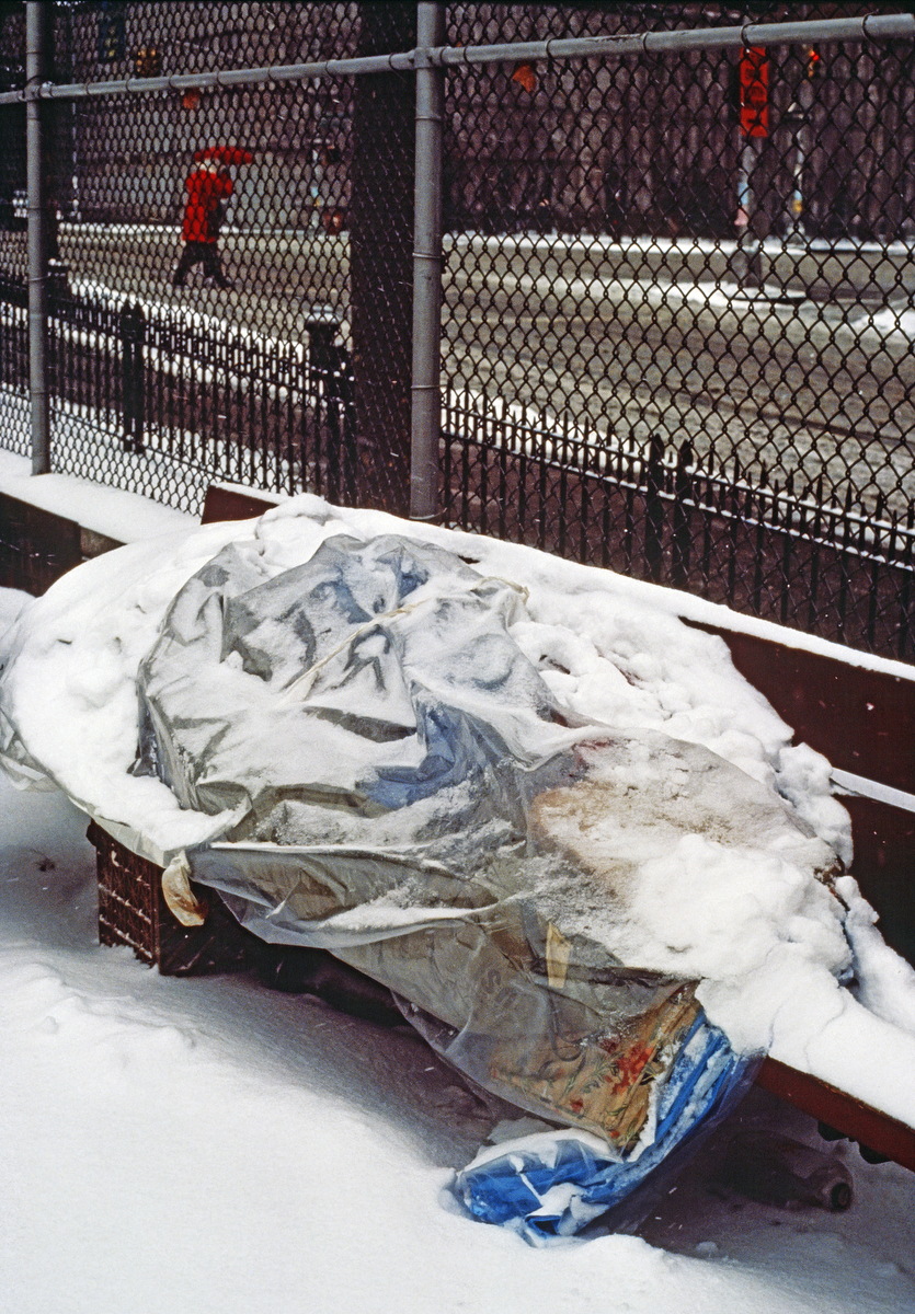 February 1988 - Homeless man covered by snow sleeps on a bench in New York City.