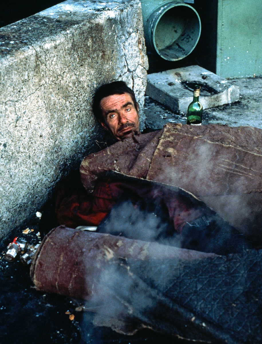1999 -  Homeless man, with his bottle of wine by his side, keeps warm by lying on top of  a steam vent during the freezing winter temperatures.