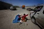 A woman and her children beg along Bagram Road, the new road leading from Kabul to the American base near the village of Bagram.
