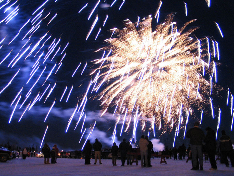 Revelers watch in amazement as fireworks light up the sky celebrating the 50th anniversary of the Caribou Carnival in Yellowknife, NWT, Canada.