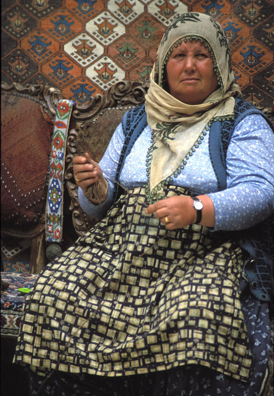 A Turkish woman works some wool at a carpet market in the Cappodochia region of Turkey.