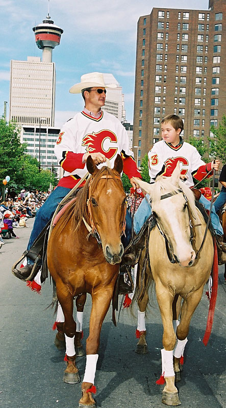 Calgary Flames GM, Darryl Sutter, rides a horse down ninth ave. with his son during the Calgary Stampede parade.