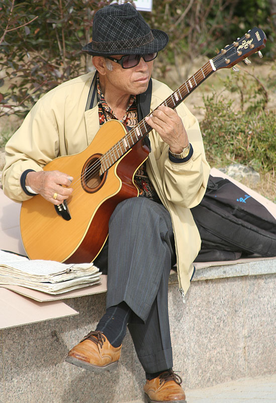 An elderly man plays his guitar while enjoying the scenery of Haeundae beach in Busan, South Korea.
