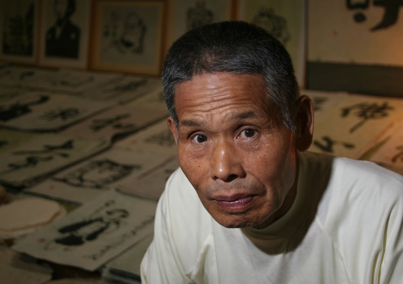 A handmade paper artisian sits in front of his work in Ino Town, on the Japanese island of Shikoku.